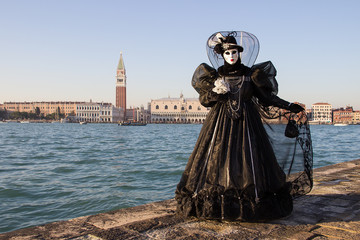 Female Venetian Mask in black dress with Venice in background, island San Giorgio, Venice, Italy