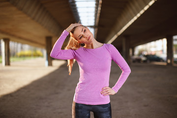 Young woman stretching neck under the bridge