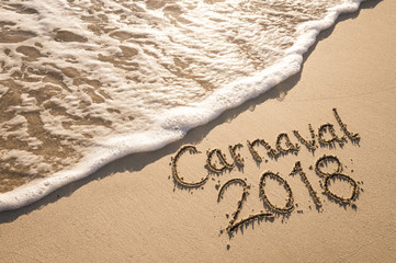 Message for Carnaval 2018 written on a smooth sand beach with a frothy incoming wave