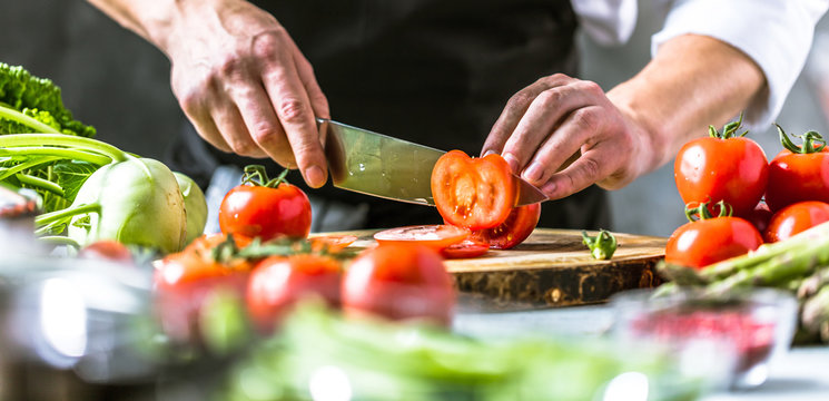 Chefkoch in der Küche mit Frischem Gemüse(Tomaten)