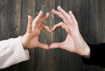Hands of a man and a girl stacked together in a heart shape