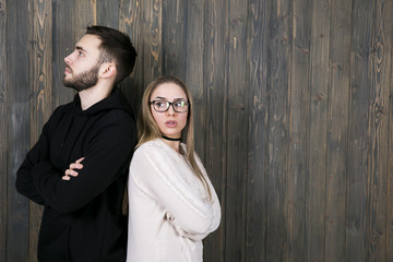 a young girl with glasses and an unshaven young man stand with their backs to each other with a serious facial expression and with arms crossed over her chest Wall mural