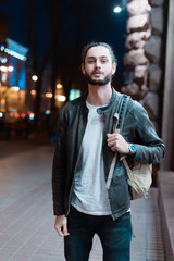 A guy with a backpack in a night city. Portrait of a bearded man in the city.