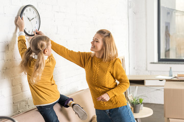 happy mother and daughter hanging clock on wall during relocation