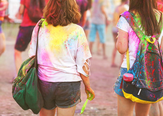 two girl celebrating the Holi festival at sunset