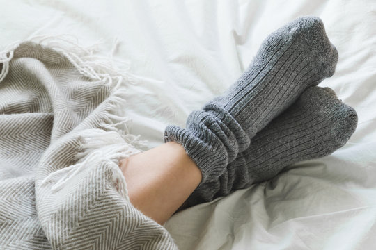 Feet up in cozy woolly pink socks with cup of tea and candles