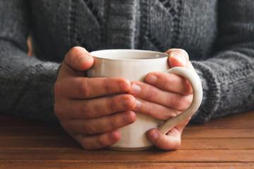 Woman holding mug of tea wearing cozy gray cardigan at a table