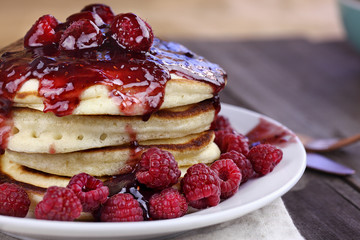 Delicious homemade golden pancakes with fresh raspberries, and raspberry syrup. Extreme shallow depth of field.