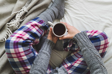Girl sat on bed in cozy pyjamas drinking a cup of tea