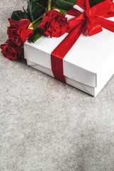 Holiday  background, Valentine's day. Bouquet of red roses, tie with a red ribbon, with wrapped gift box. On a gray stone table, copy space