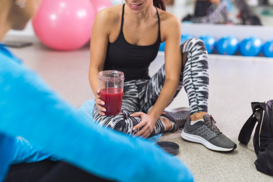 Woman taking a break in gym and drinking smoothie drink