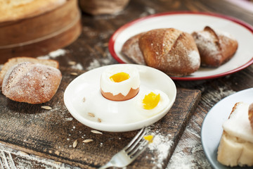 boiled egg on a plate and freshly baked bread on a wooden table