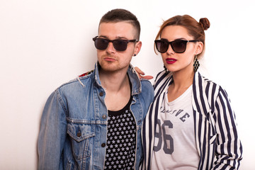 fashion couple in sunglasses lies on a white background, smiling happily and surprised. Vogue Style