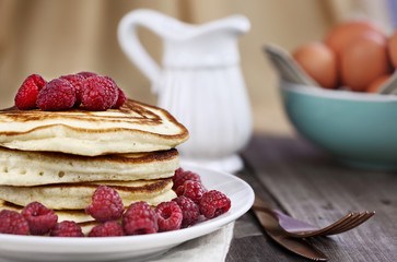 Delicious homemade golden pancakes with fresh raspberries. Extreme shallow depth of field.