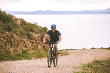 Theme tourism and cycling on mountain biking. guy rides uphill on a rocky, rocky road against the background of the Mediterranean Sea in Spain on the shore of the kosta brava in helmet and sportswear