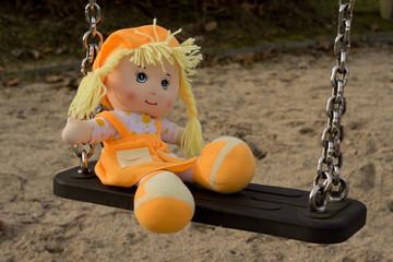 Obraz Lalka siedząca na huśtawce - fototapety do salonu