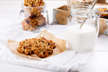 Healthy oatmeal cookies with raisins on white table.