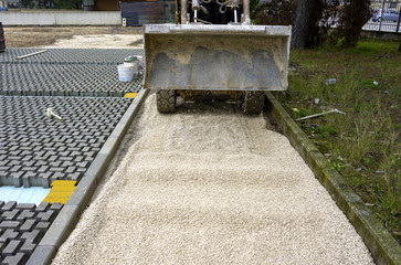 skid loader distributes grit and sand for the background of the pavement paving