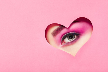 Conceptual photo of Valentine's day. Eye of Girl with Festive Pink Makeup. Paper heart on a pink background. Love symbols Valentines day
