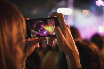 woman using mobile phone taking photo of live show concert with blurry stage as background. have a copy space for text.