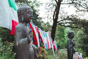 two statues of buddha in a garden connected by different national flags