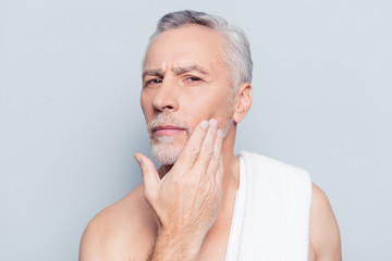 Dermatology pampering procedure rejuvenation wrinkles concept. Close up portrait of concentrated suspicious attentive man analyzing the skin condition touching with hand isolated on gray background