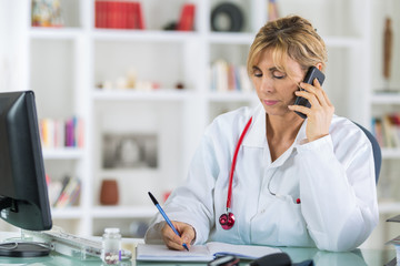 middle-age female doctor on phone at office