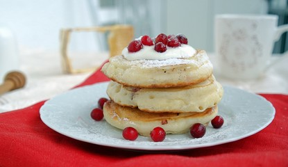 Pancakes with cranberries and sour cream, sprinkled with powdered sugar