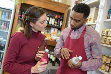 salesman in supermarket offering bottle of to woman