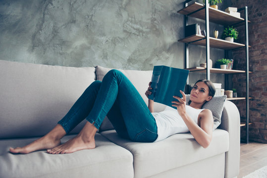 Pretty, charming woman in jeans laying on sofa, holding in hand textbook, reading book, preparing for exam, lesson, learning new material