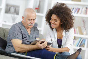 carer and senior man with tablet sitting on the sofa