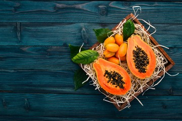 Papaya and Kumquat. Tropical Fruits. On a wooden background. Top view. Copy space.