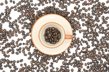 top view closeup of a coffee cup filled with roasted coffee beans o of roasted coffee beans isolated on white background .