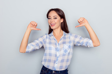It is me! Portrait of smiling cheerful nice young woman in checkered shirt pointing thumb fingers at her body isolated on grey background, proud of herself, having ego