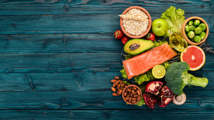 Healthy food. Fish salmon, avocado, broccoli, fresh vegetables, nuts and fruits. On a wooden background. Top view. Copy space. Wall mural