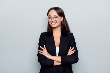 Portrait of young, caucasian, stunning, nice stylish, sexy headmistress in black jacket, formal wear with crossed arms and beaming smile standing over grey background