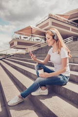 Vertical profile side view photo of attractive cheerful careless stylish wearing casual jeans white tshirt blonde woman enjoying the sound in her earphones, using mobile and drinking takeaway tea