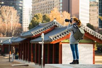 A woman traveler photographs an ancient palace in South Korea