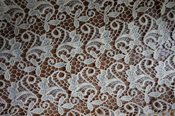 Openwork ivory lace on wooden table from above