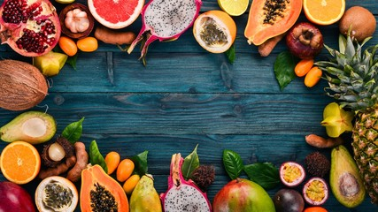 Tropical fruits, papaya, Dragon Fruit, rambutan, tamarind, cactus fruit, avocado, granadilla, carambola, kumquat, mango, mangosteen, passionfruit, coconut. On a wooden background.