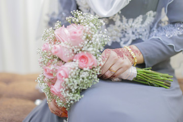 Bride hand with henna and a bouquet of flower.
