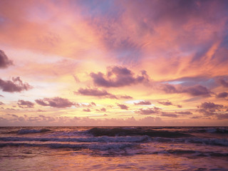 Colorful sunset on the tropical beach with beautiful sky, clouds, soft waves.