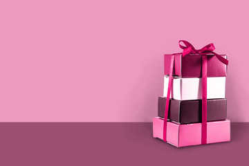 Gift boxes stacked on a pink background with copy space, concept for Valentine's Day, Mother's Day, Christmas, birthday and anniversary.