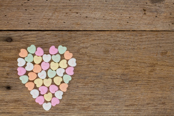 Heart filled with conversation hearts on barn wood