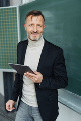 Confident teacher holding a tablet in classroom
