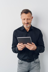 Man smiling while reading information on a tablet