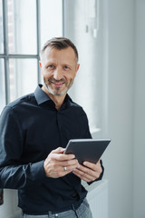 Portrait of a happy man holding a tablet PC