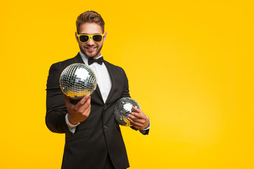 Young man in suit with disco balls