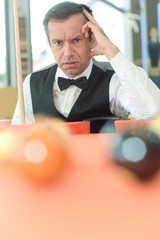 thoughtful man with suit sitting posing in billiard pool