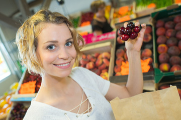 beautiful woman choosing ripe organic cherries